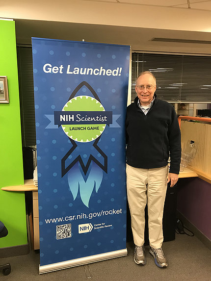 """Lucketts stands to the left of a banner that reads, """"Get Launched! NIH Scientist Launch Game"""" along with the web address for the game."""