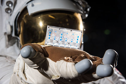 A person in an astronaut suit holds up a tissue chip