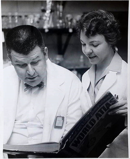 Black & white image of Stohlman and Judith McKay Sides looking at book
