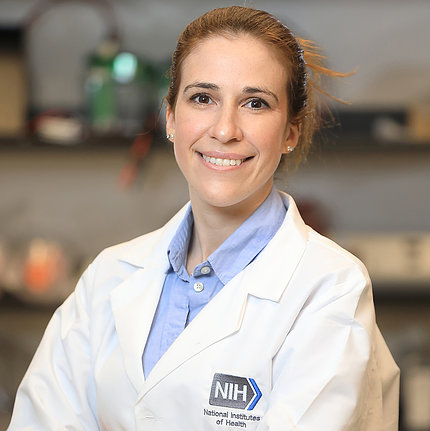 A smiling Sadtler, in white lab coat with NIH logo, standing in the lab