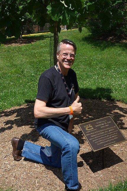 Bruce Lee gives thumbs up as he kneels, smiling next to the tree and memorial plaque honoring his late son, on the south lawn of the Clinical Center.