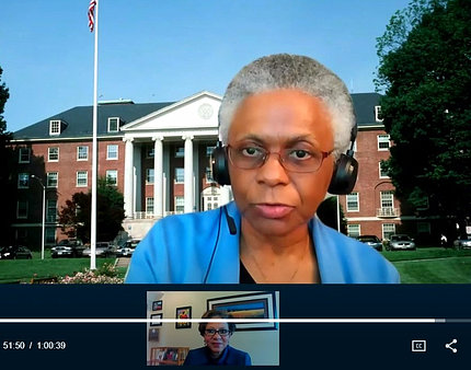 Dr. Marie Bernard speaks virtually in front of image of Bldg. 1 on NIH's campus.