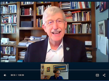 A smiling Dr. Collins speaks on video surrounded by books in his home office.