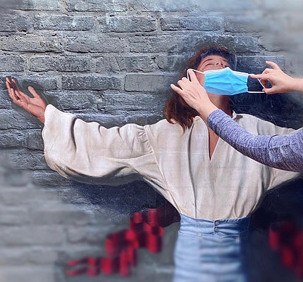 Person posed with outstretched arms, back to a wall, while a pair of hands places a mask over the person's nose & mouth