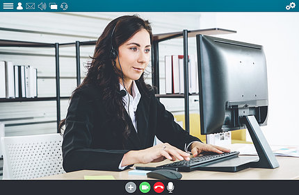 Woman seated at desktop computer and keyboard.