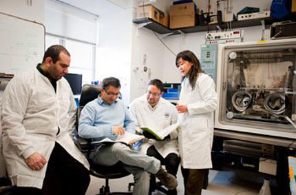 Three members in white coats stand around Bharti while Bharti reads from a notebook in his lab