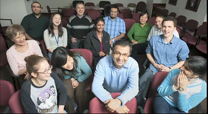 Bharti and his lab share a laugh with each other while sitting in a conference room.
