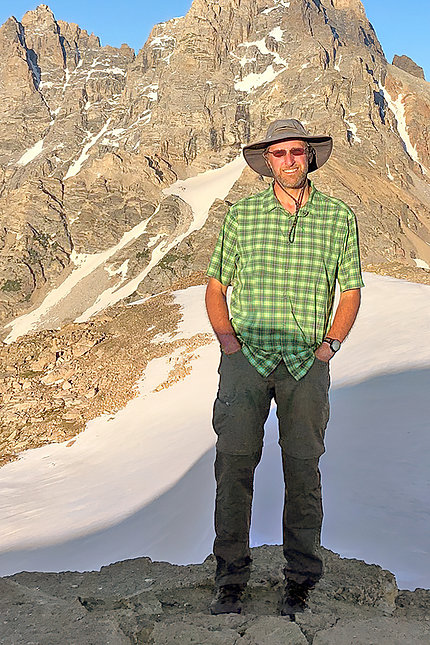 Kercher in sunshades and sunhat with wide brim, with mountains behind him