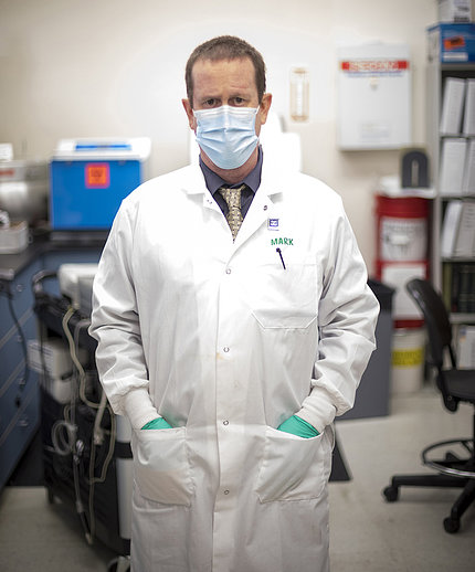 Pandori stands in long white lab coat and mask in the lab.