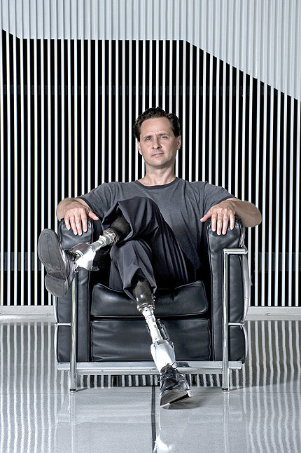 Herr sits facing forward with his legs crossed.