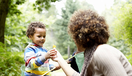Smiling toddler boy is handed a flower by adult woman whose back is toward the camera.
