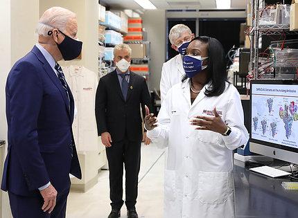 In lab, Corbett briefs President Biden as others look on.