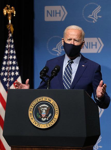 Behind presidential seal, Biden speaks from podium.