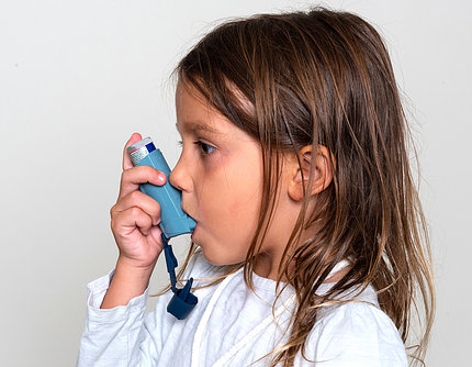 A young girl holds a blue inhaler to her mouth.