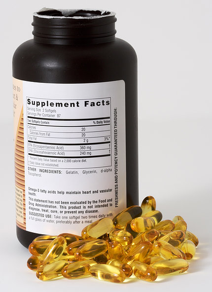 Yellow capsules lay beside a bottle, showing the ingredient label