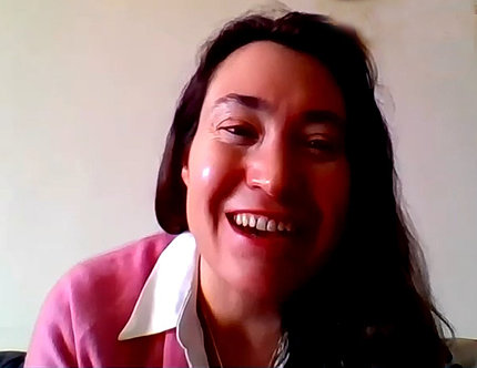 A smiling Cecile Viboud in pink shirt with white collar speaks from her home.