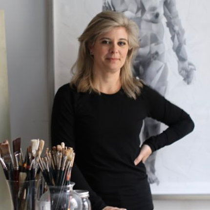 Hill-Edgar stands in front of artwork mounted on wall and behind a table with paintbrushes in foreground