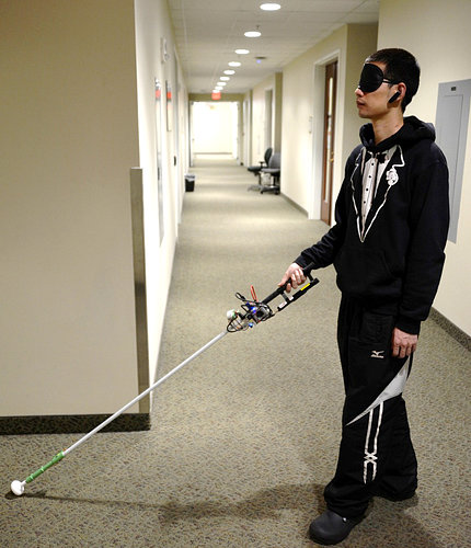 Man in blindfold with cane device in hand stretched out in front of him