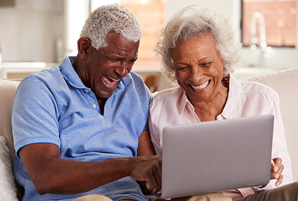 Gray-haired Black couple smiling behind a laptop