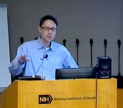 Chow speaks from a podium branded with the NIH logo