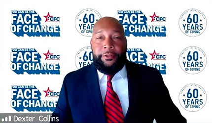 screenshot of head and shoulders of Black man wearing suit and tie, with CFC logos and slogans on wall behind him
