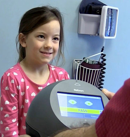 Young girl smiles as round black device with screen shows result to unseen clinician.