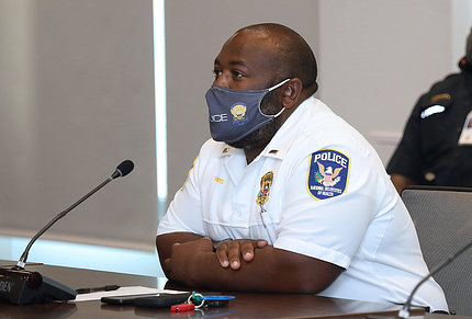 Black male in uniform and facemask, seated at conference table