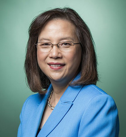 Head shot of a smiling Grace Ma, wearing a light blue suit