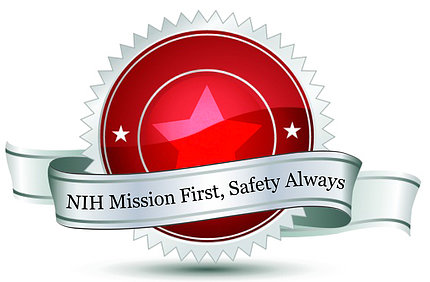 A red circular seal with two stars and surrounded by white trim has a ribbon that reads: NIH Mission First, Safety Always