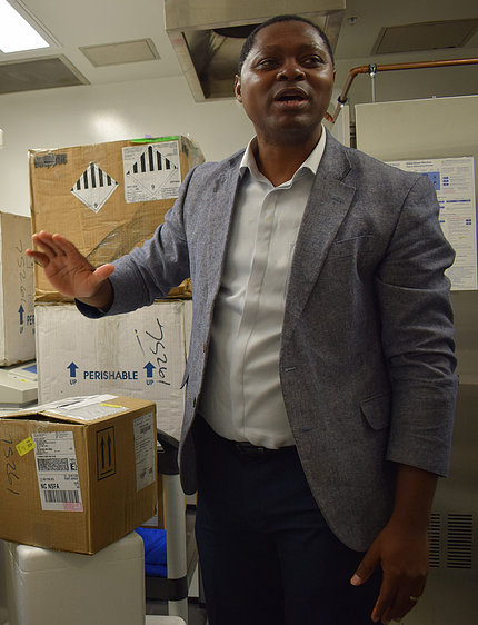 Agbor-Enoh stands with his palm extended, near large boxes of supplies.