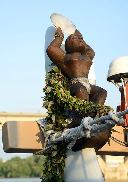 A statue tied onto the back of the boat guards the vessel.