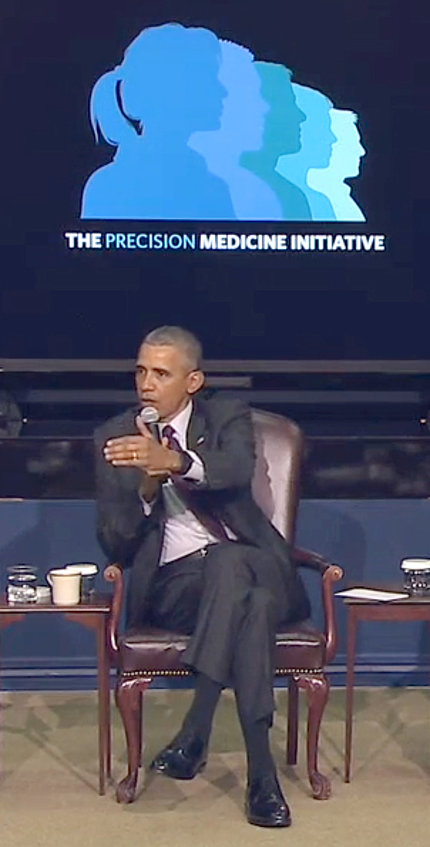 President Barack Obama partiWith mic in one hand, Obama gestures with other hand while seated in front of a projected slide.cipates in PMI summit panel Feb. 25 at the White House.