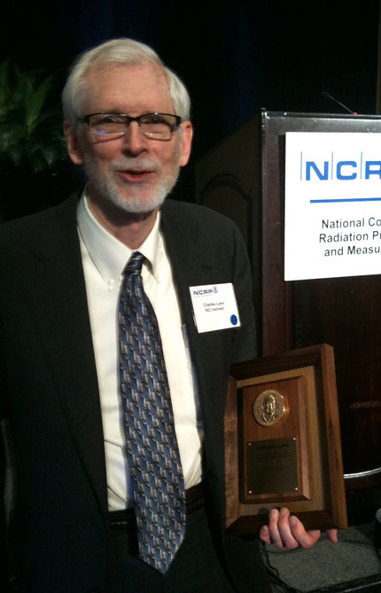 Dr. Land poses with honorary plaque