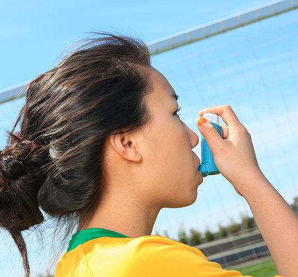 A girl using an asthma inhaler on the soccer field.