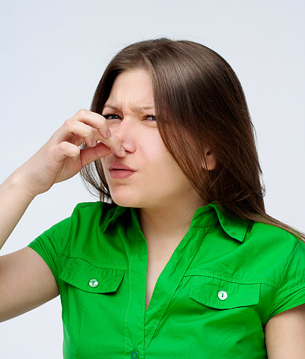 A young woman holding her nose because of an odor.