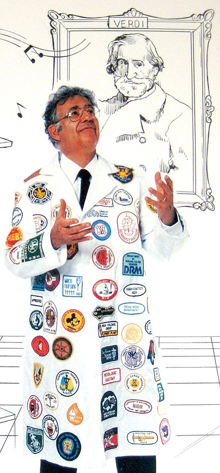 Rosen wears a lab coat with logos while standing in front of a cartoon portrait of Verdi