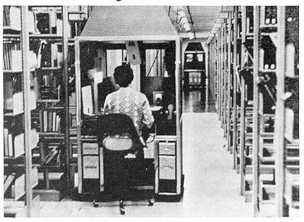 Back of woman seated at microfiche table, among rows of files