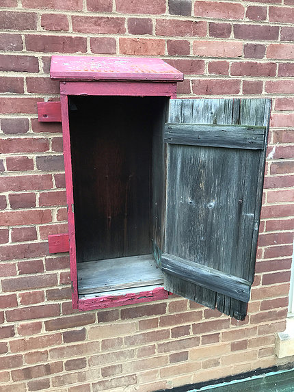 A red wooden rectangular box attached to a brick wall