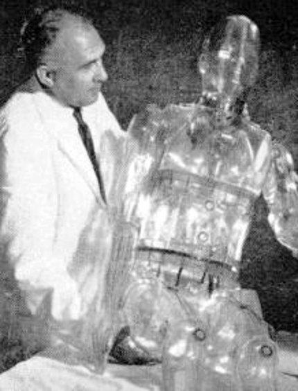 Man in labcoat holds transparent mannekin.