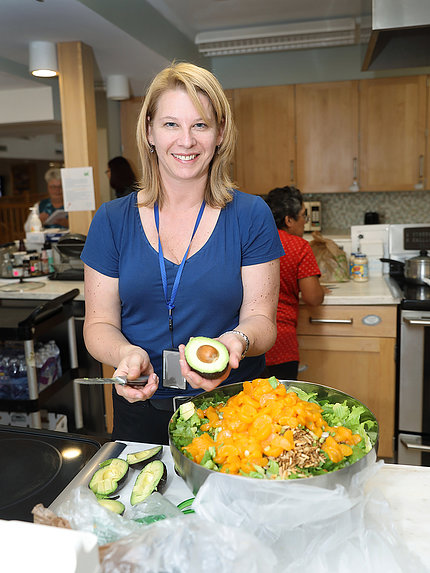 Gardner smiling, slicing avocado behind big bowl of salad