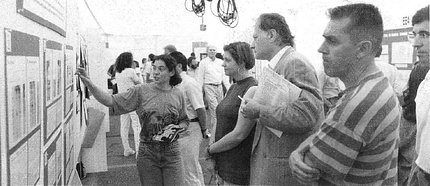 Black and white image of NIH investigators showing their research posters to colleagues.