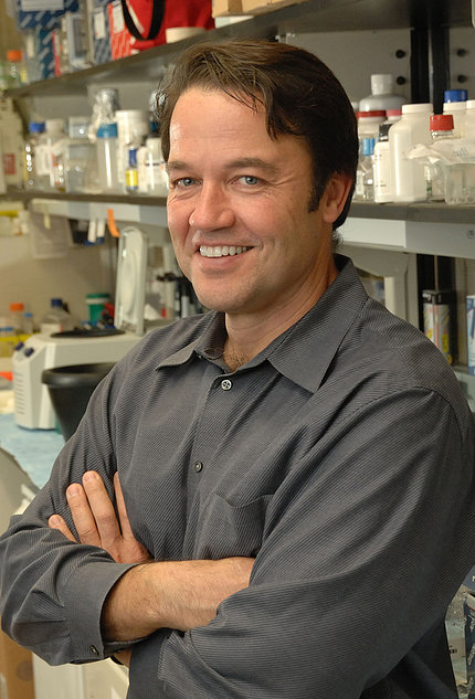 A smiling Dr. Tisdale stands, arms folded, in his lab.