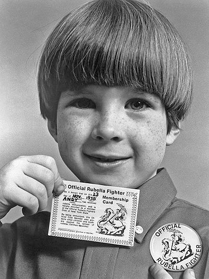 "Child proudly displays his ""official rubella fighter"" card and button."
