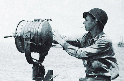 In uniform with helmet, Gardner operates a giant spotlight during WWII.