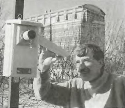 Black & white photo of Mueller inspecting a birdhouse.