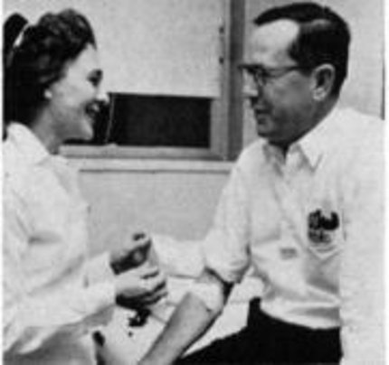 Nurse chats with patient at Blood Bank.