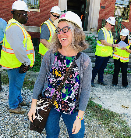 Dr. Sarah Leavitt wearing a hard hat stands on a construction site.