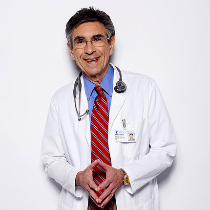 Dr. Robert Lefkowitz stands with fingertips pressed together, wearing white lab coat