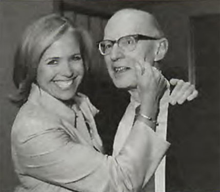 A black-and-white photo of a smiling Katie Couric pinching the cheek of then-NCI director Dr. Alan Rabson.