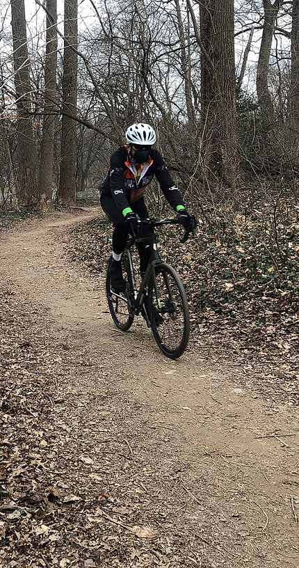 Kern in mask and helmet, riding bicycle on path through wooded area
